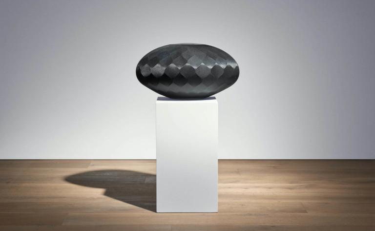 A black, geometric wireless speaker on a white pedestal.