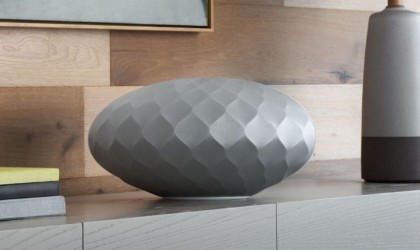 A gray geometric wireless speaker on a table.