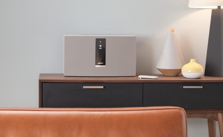 A wireless speaker on a living room credenza.