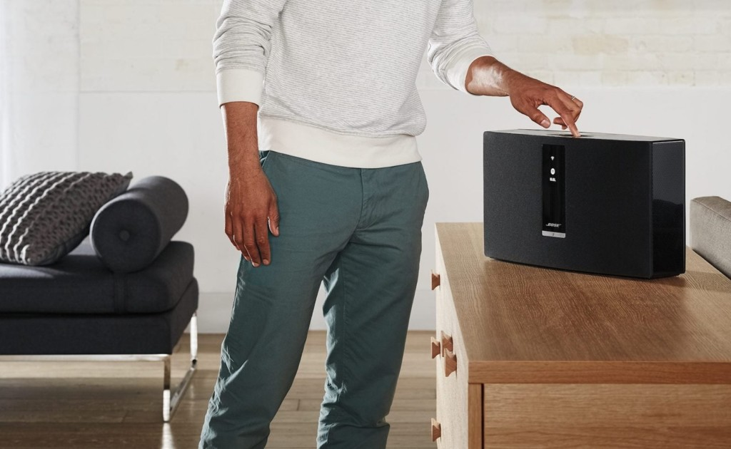 A man pressing a button on a black wireless speaker