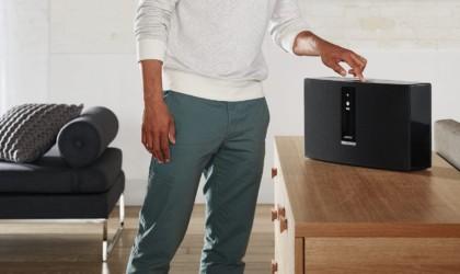 A man pressing a button on a black wireless speaker