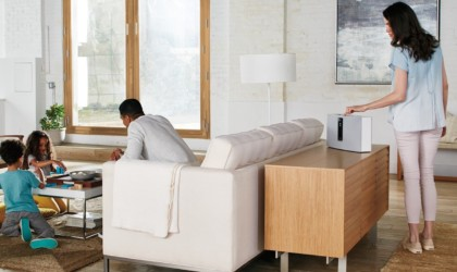 A man sits on a white couch while a woman presses a button on the white wireless speaker behind him.
