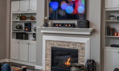 A wireless speaker soundbar and TV above a fireplace