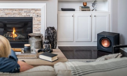 A wireless speaker subwoofer on the floor in the corner of a living room.