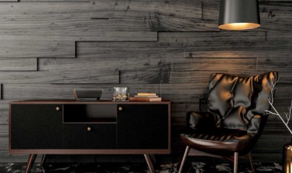 A wireless speaker on a credenza, a chair and lamp next to it.