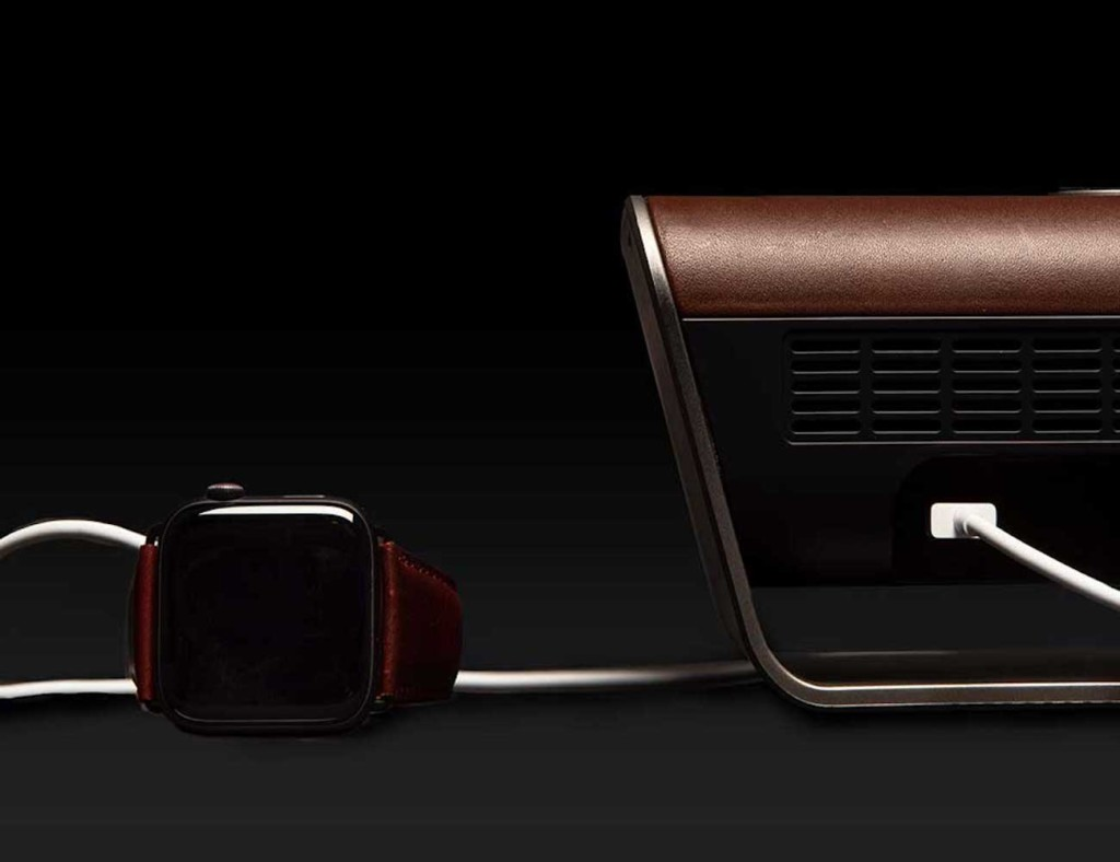 A wireless speaker with a smartwatch next to it.