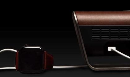 A wireless speaker with a smartwatch next to it.