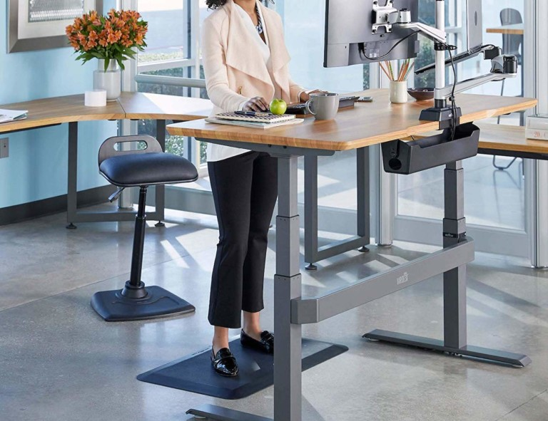 Woman standing at desk with standing desk chair