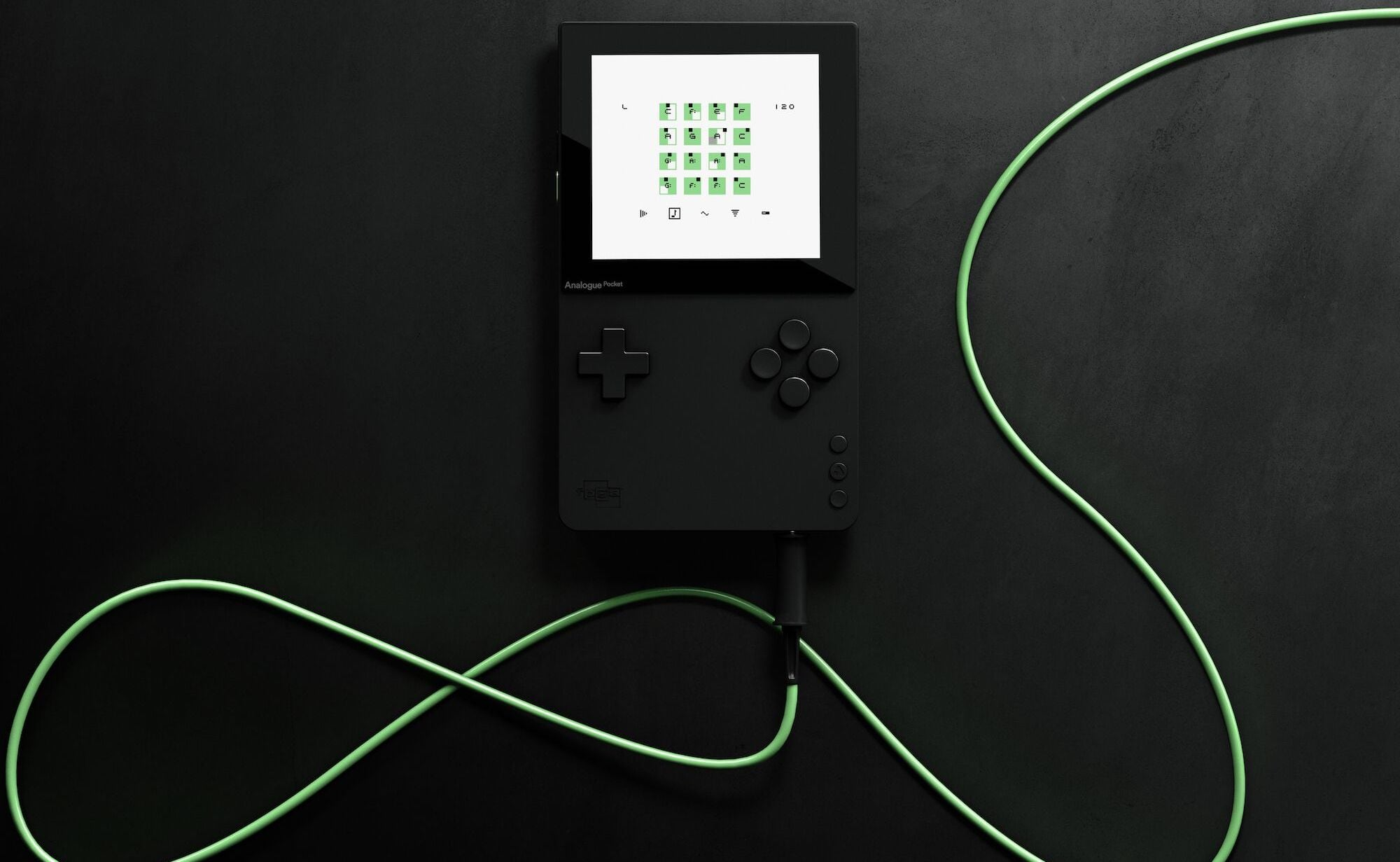 The black handheld video game system with its green cord displayed around it