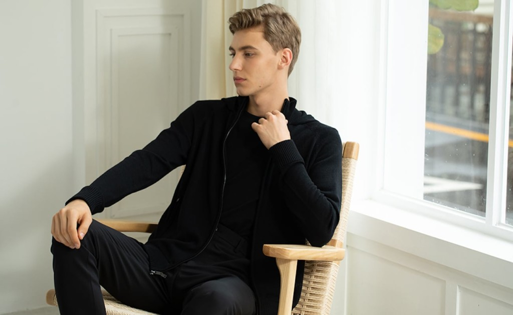 A man sitting in a chair, wearing a black eco sweater.