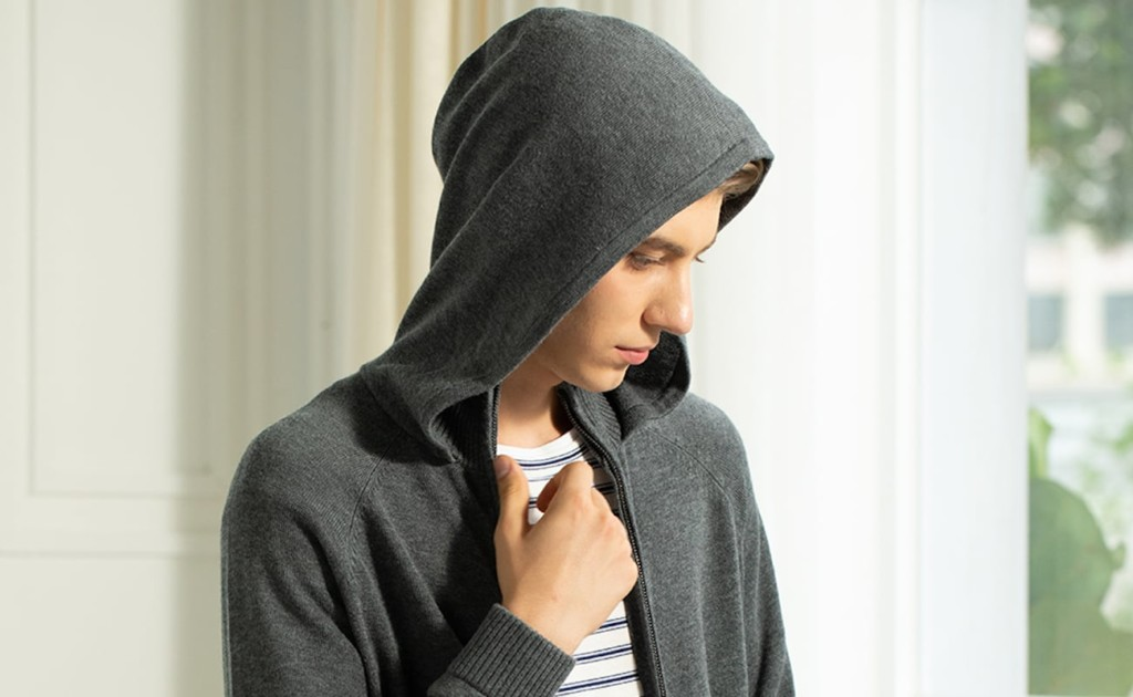 a man wearing a gray eco sweater, with the hood up over his head.