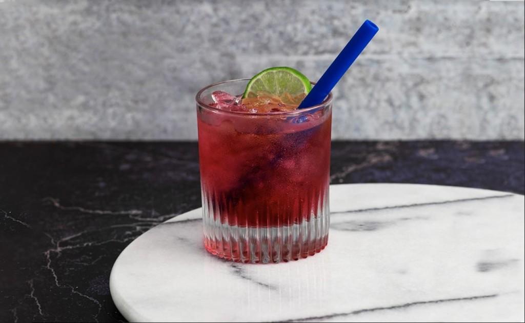 An dark blue environmentally friendly straw in a cocktail.