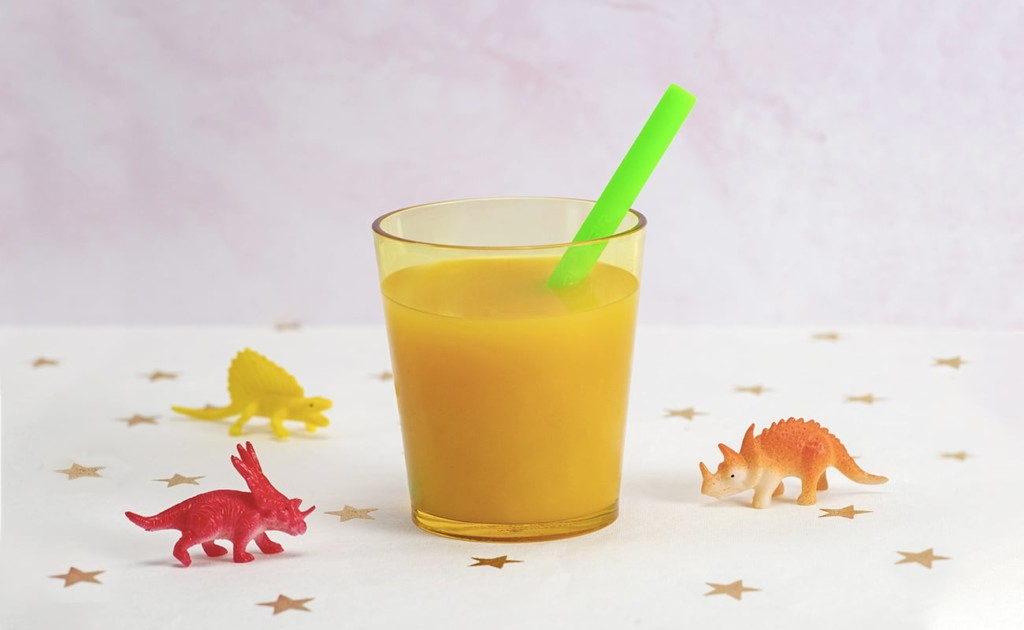 A neon green environmentally friendly straw in a glass of orange juice, surrounded by toy dinosaurs.