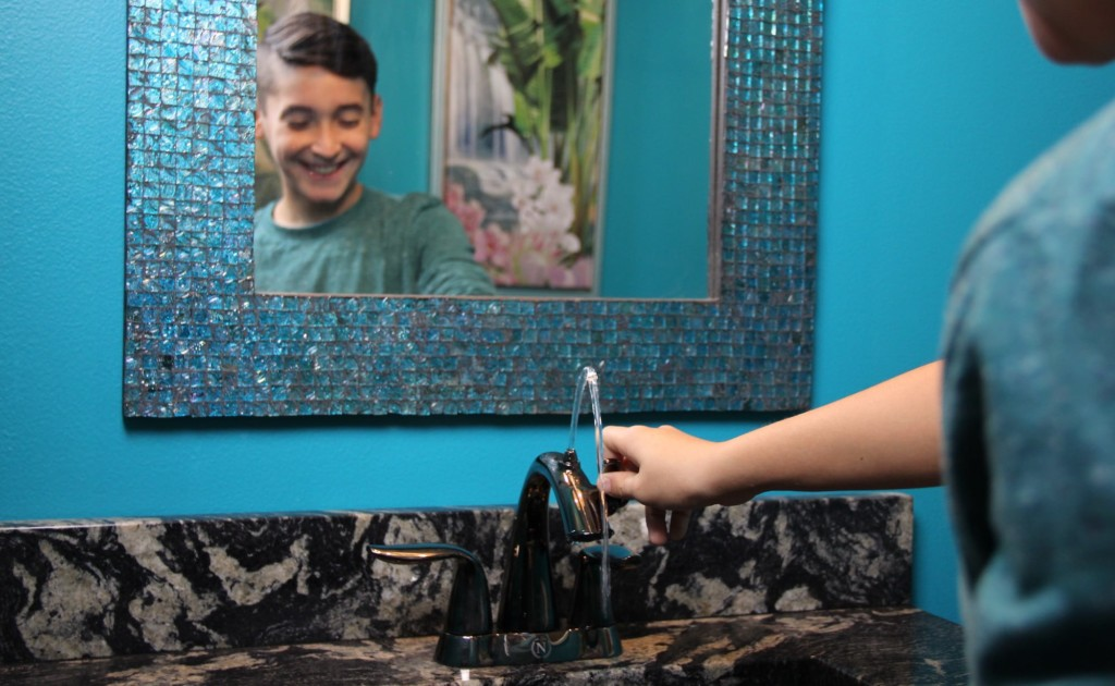 A little boy using an eco-friendly faucet.