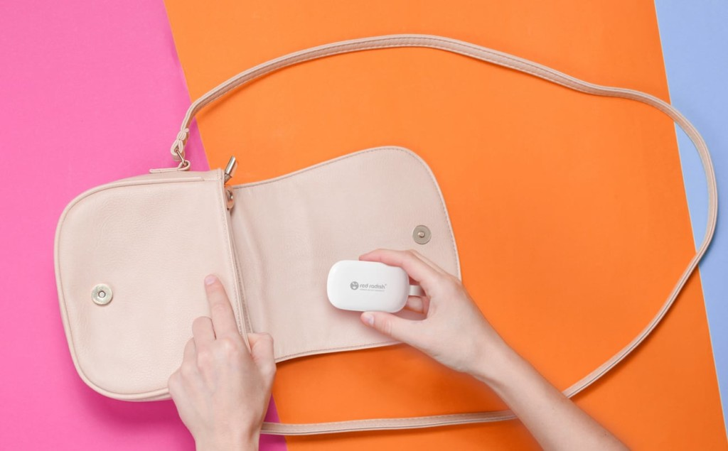 woman putting a small white compact charging set into a pale pink purse.