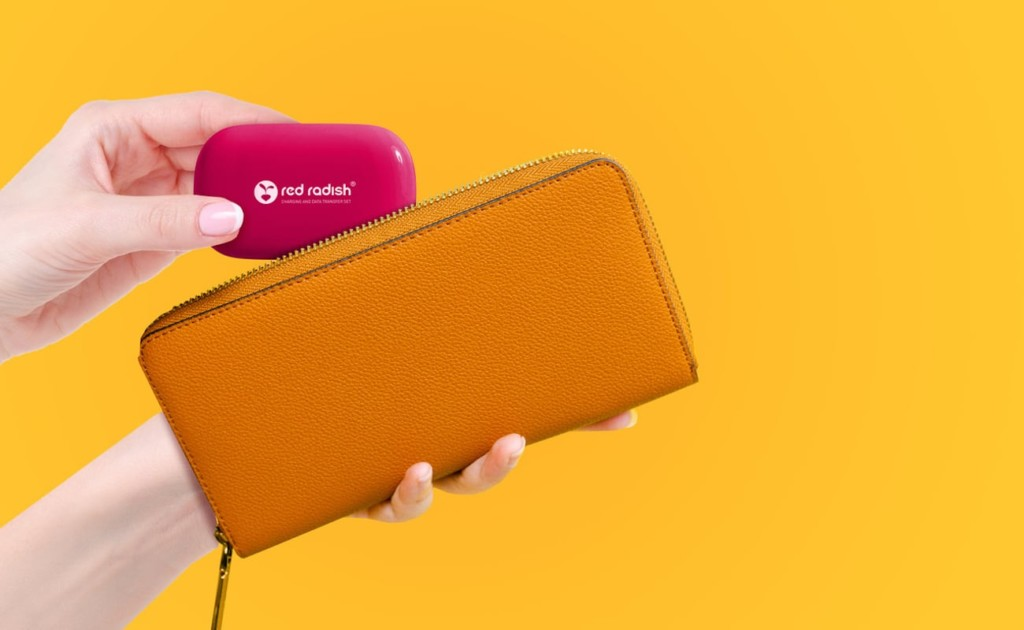 A woman placing a dark pink compact charging case into a brown wallet, against a yellow background.