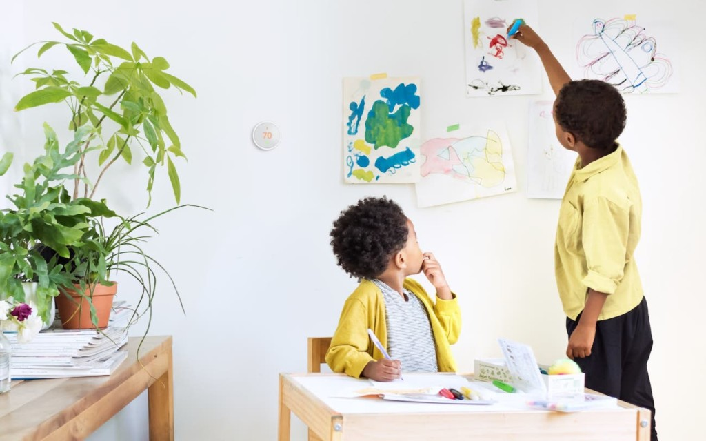 Two little boys playing in an art room, a smart home thermostat on the wall behind them.