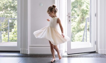 A little girl in a ballet dress, a smart home thermostat on the wall behind her.