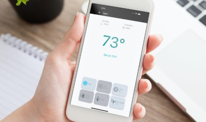 A hand holding a smartphone with a smart home thermostat app pulled up.