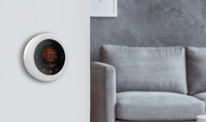 A round smart home thermostat on a wall, with a chair in the background.