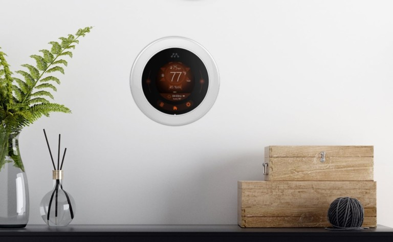 A round smart home thermostat on a white wall.