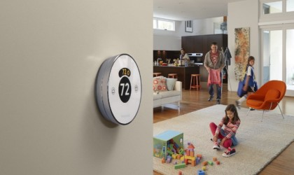 A side view on a smart home thermostat on a wall, with children playing in the background.