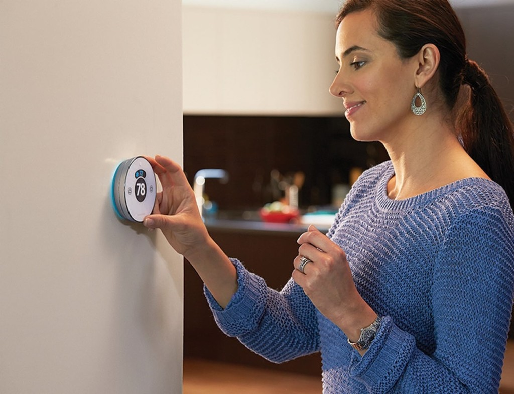 A woman adjusting a smart home thermostat.
