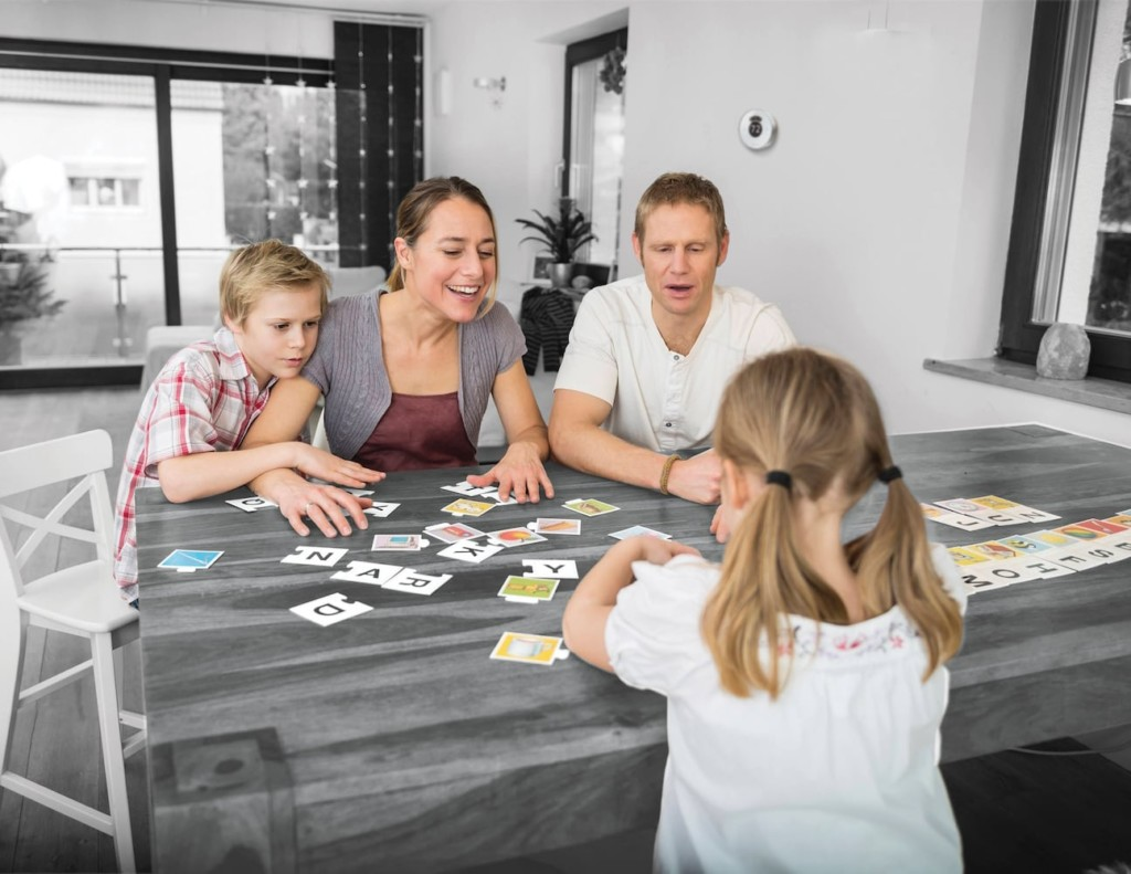 A family playing a game at a table, a smart home thermostat on the wall behind them.