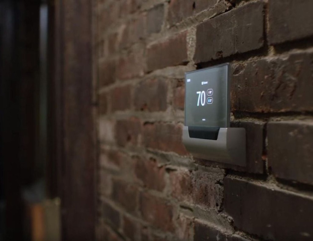 A side view of a smart home thermostat on a brick wall.