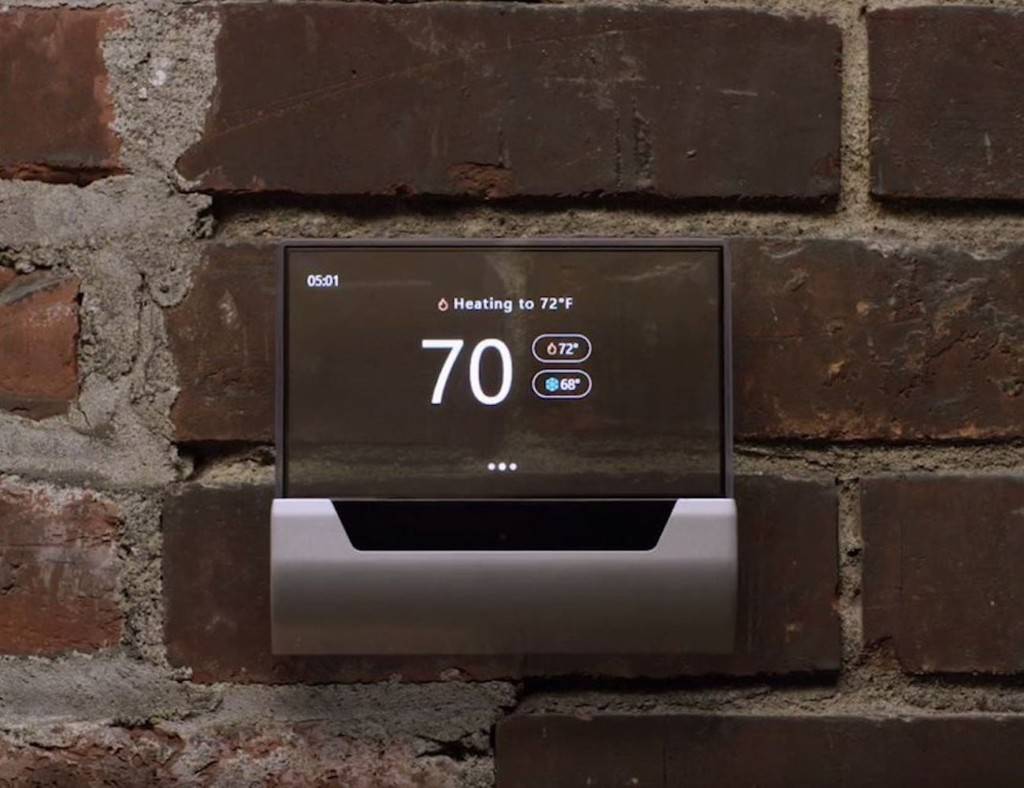 A smart home thermostat attached to a brick wall, showing a temperature readout.