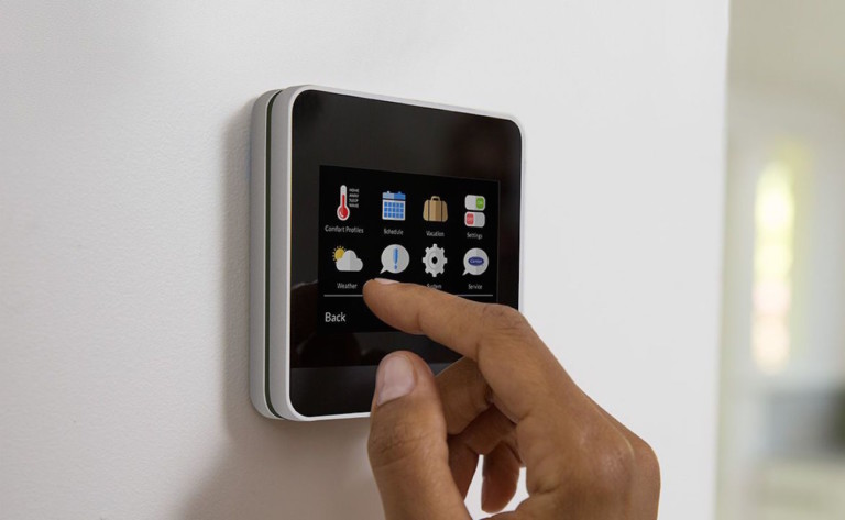 A finger pressing a smart home thermostat screen