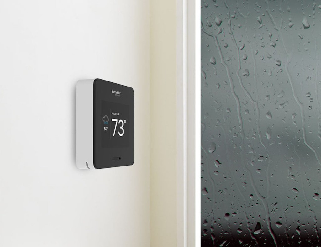 A side view of a smart home thermostat on a white wall.