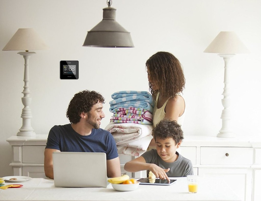 A family is in the kitchen, a smart home thermostat on the wall behind them.