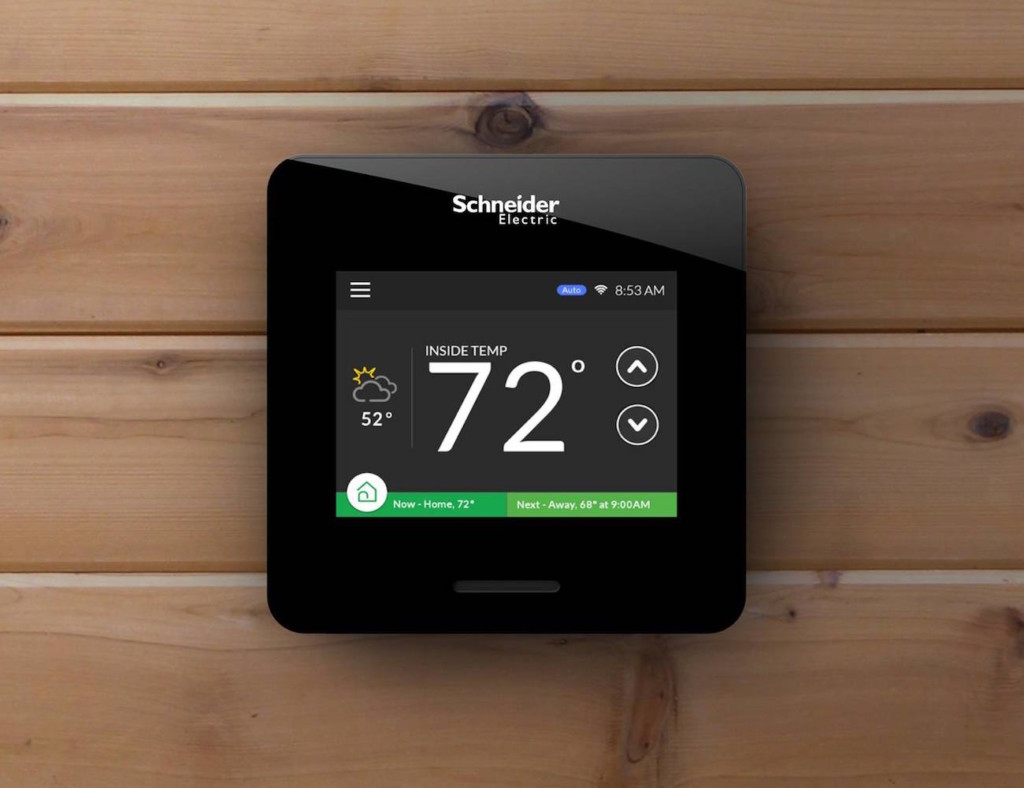 A smart home thermostat showing the display settings, on a wood background.