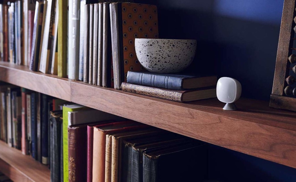 A small white smart home thermostat sensor on a bookcase.