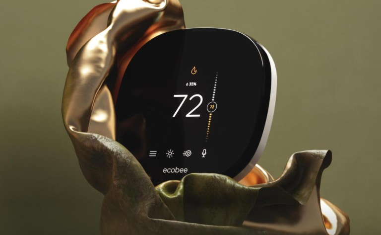 A round, black smart home thermostat nestled in an olive green vase.