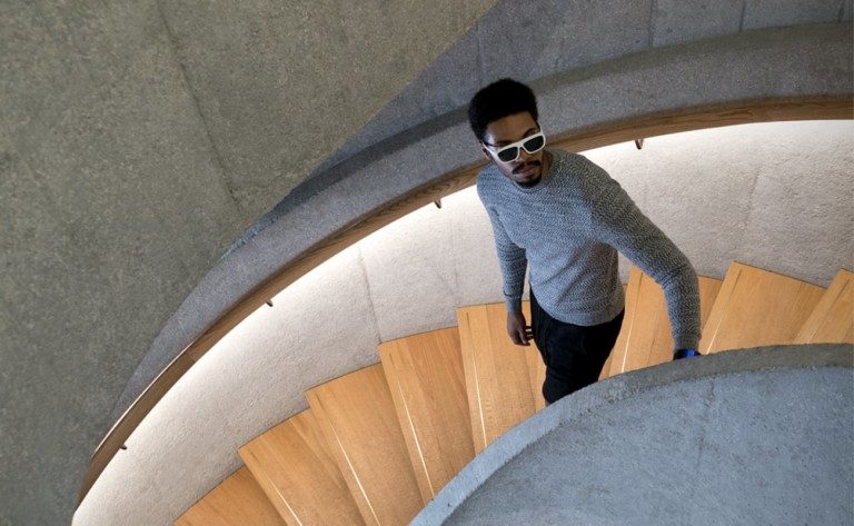 Man in smart glasses walking down curved staircase