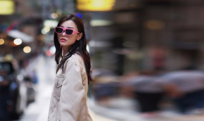 Woman in pink smart glasses and jacket is in focus in a blurred city background