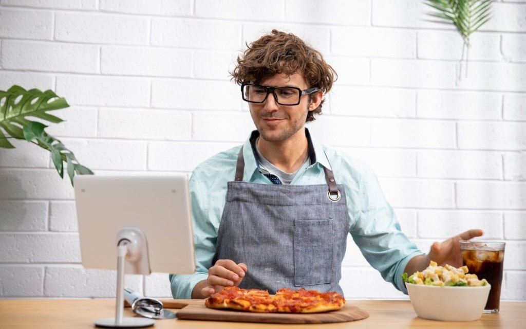 Man in a kitchen with tablet and smart glasses, wearing an apron