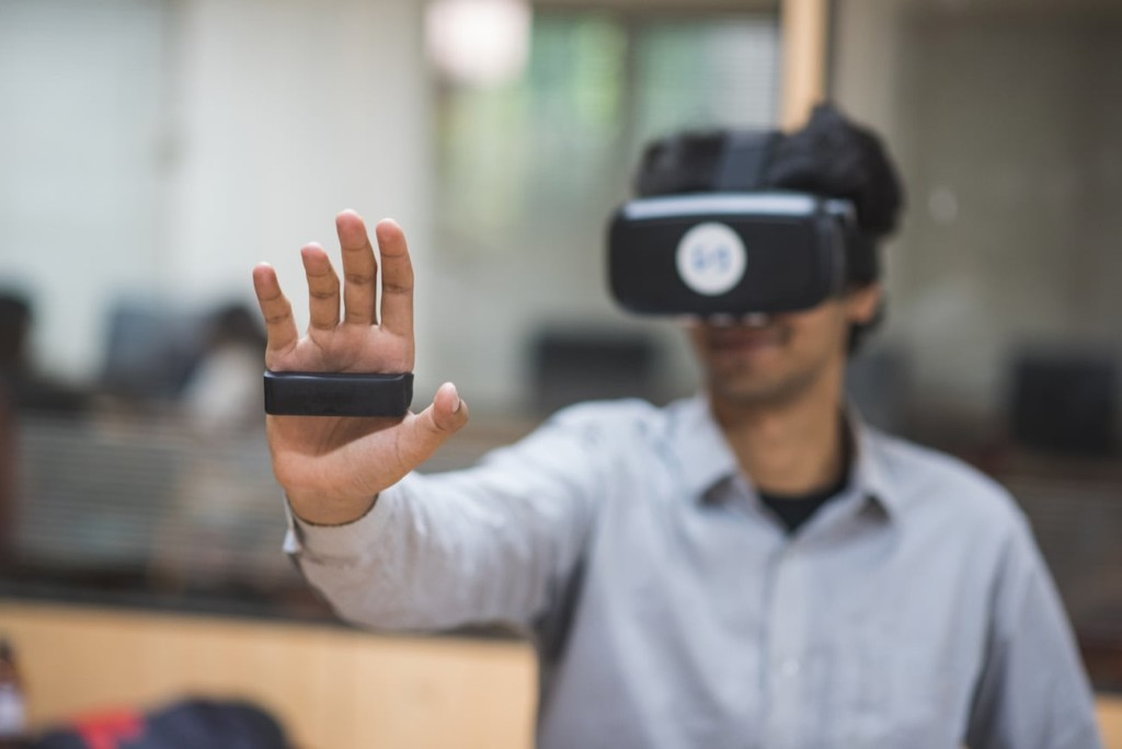 Man wearing VR headset and using a gesture-based controller in his hand