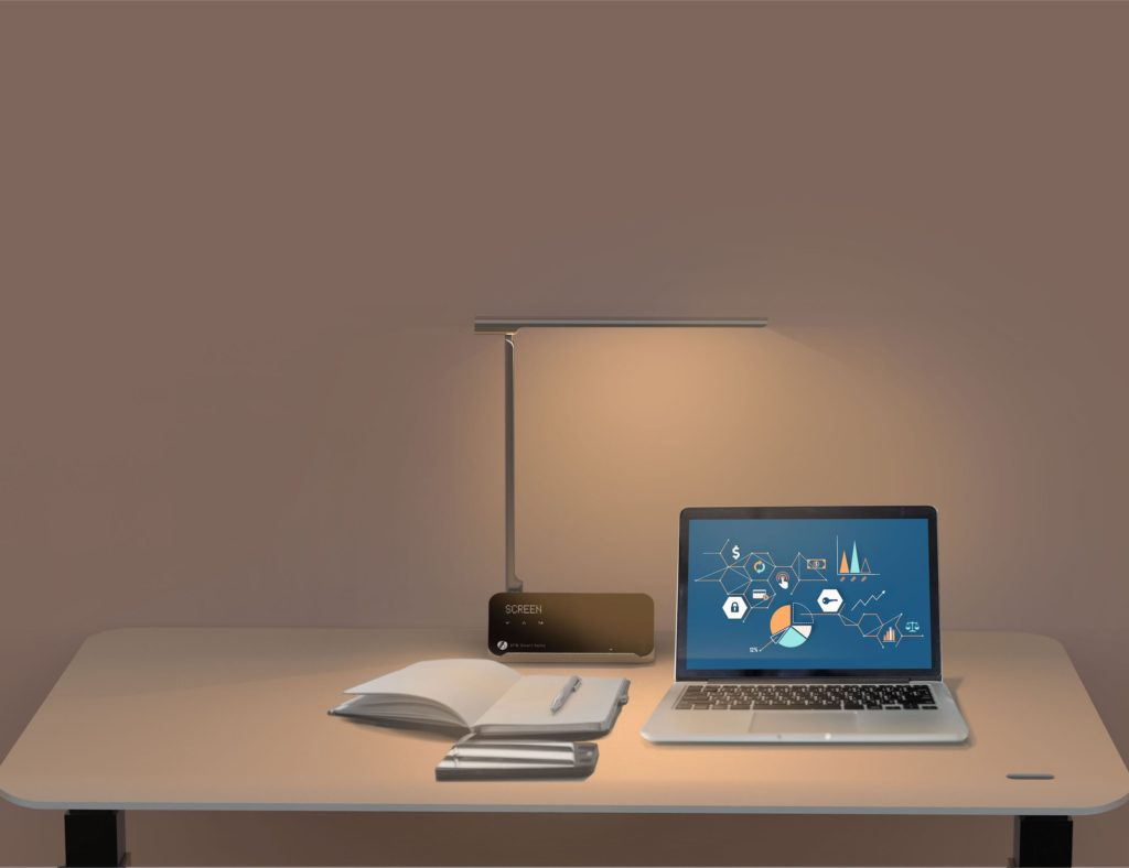 Minimalist desk setup with open laptop and illuminated lamp