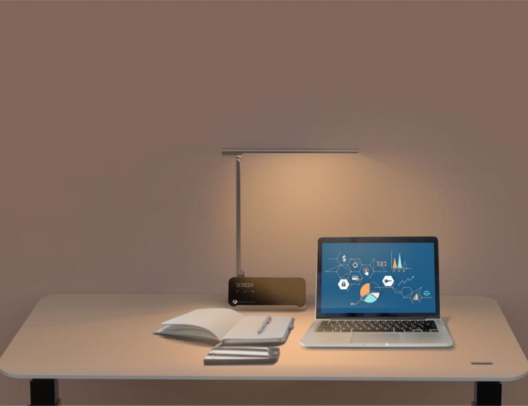 Minimalist desk setup with open laptop and illuminated lamp