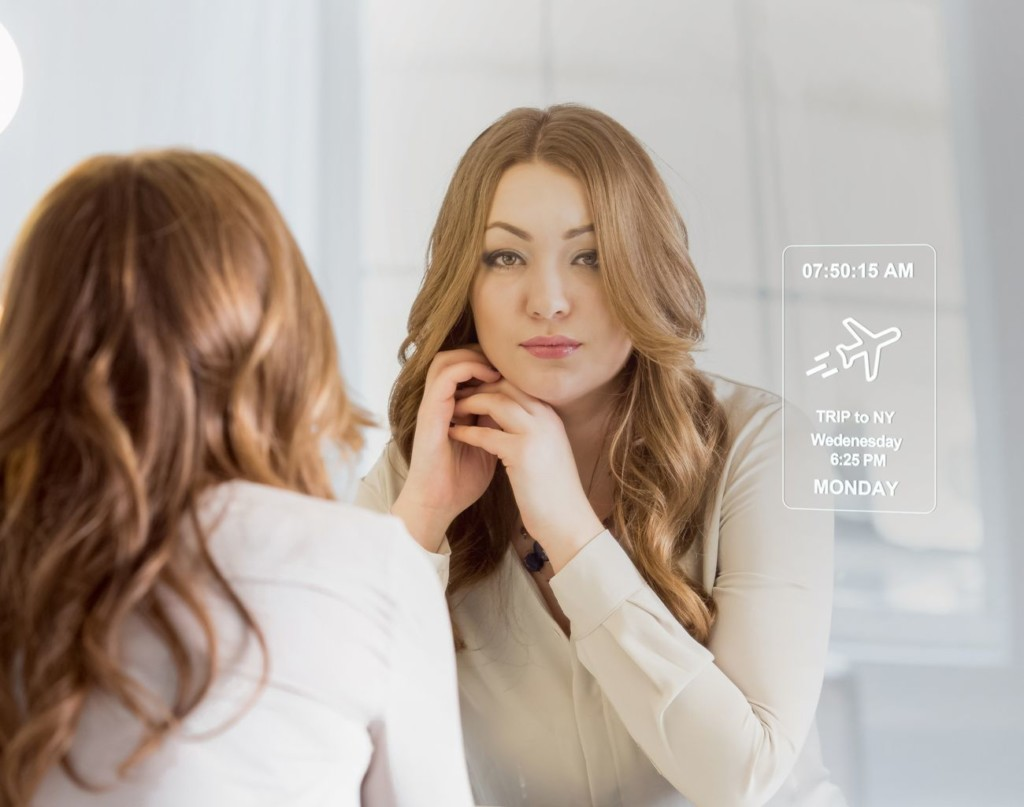 Woman fixing hair looking into smart mirror
