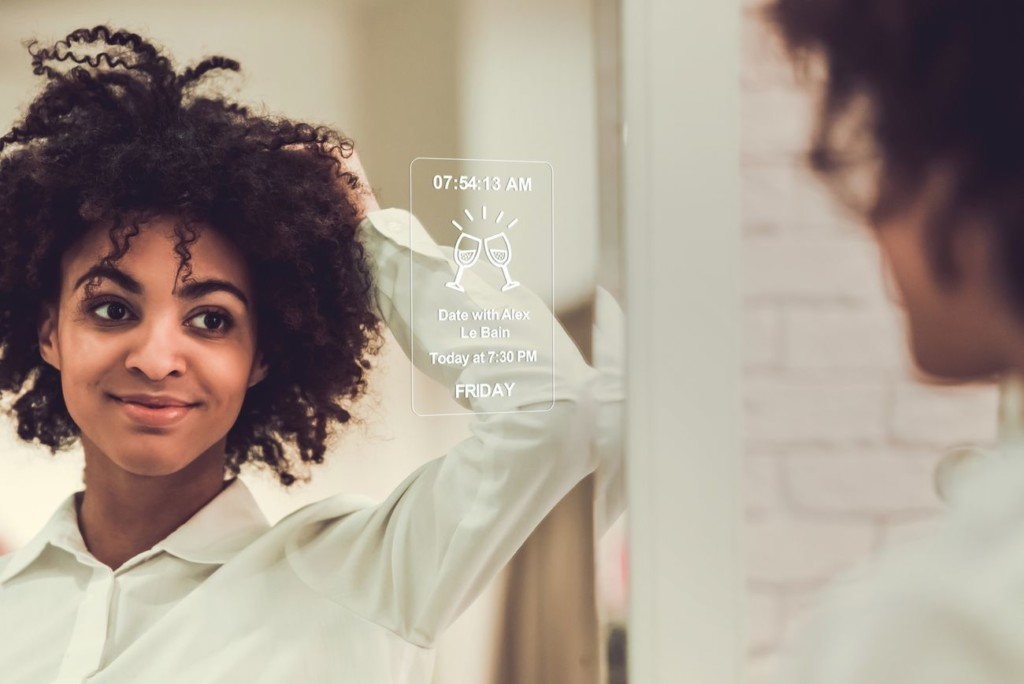 Smiling woman adjusting hair looking into smart mirror