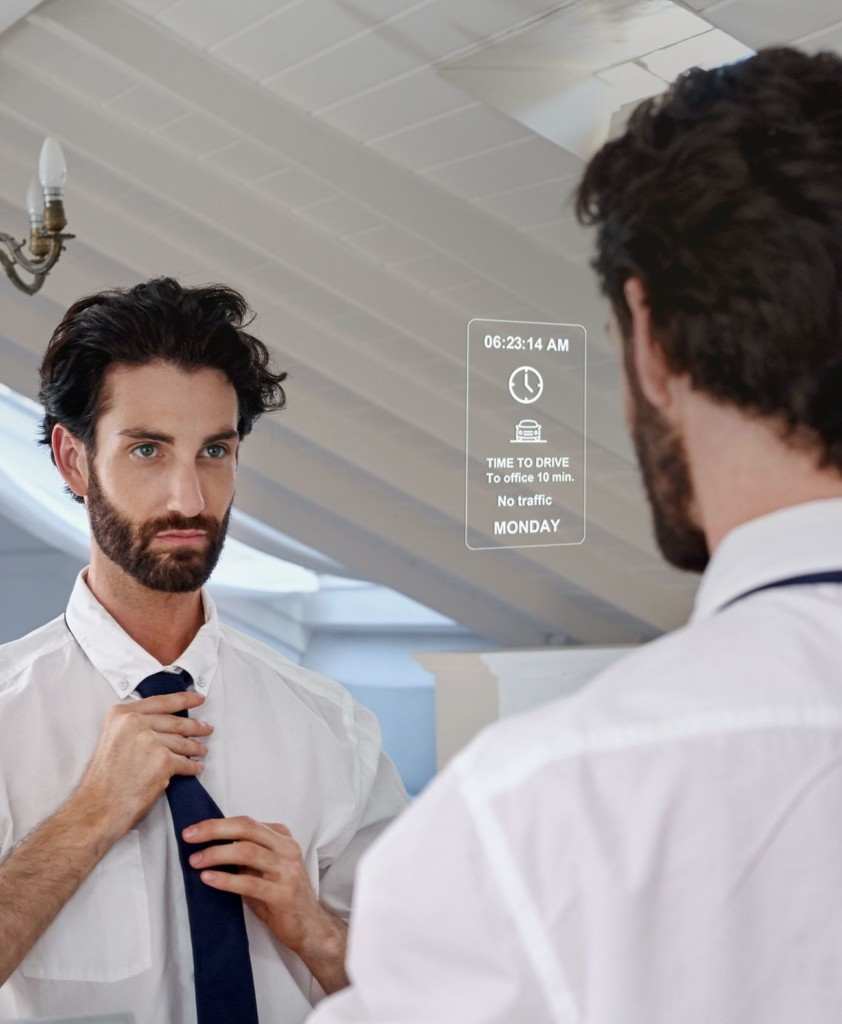 Man fixing his tie while looking into a smart mirror