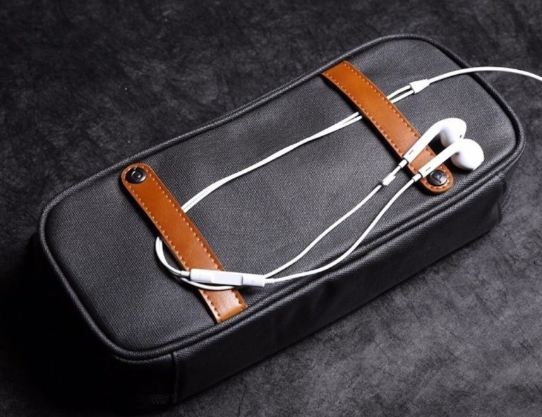 A close useful office gadgets organizer bag with a pair of earbuds on top of it.