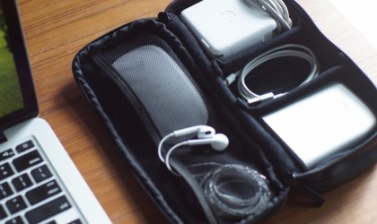 An open useful office gadgets organizer bag with various cords and chargers inside.