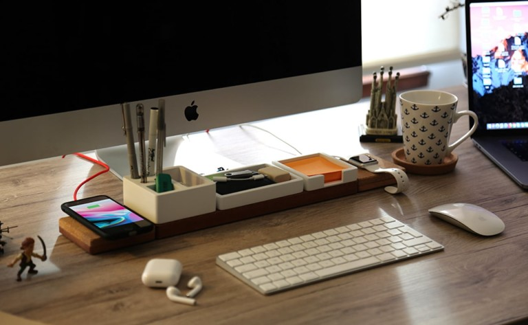 A keyboard in front of a useful office gadgets wireless charging station desk organizer.