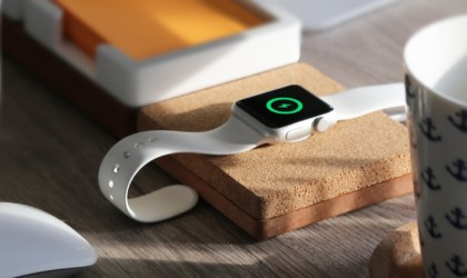 A close up of an iWatch on top of a useful office gadgets wireless charger desk organizer.