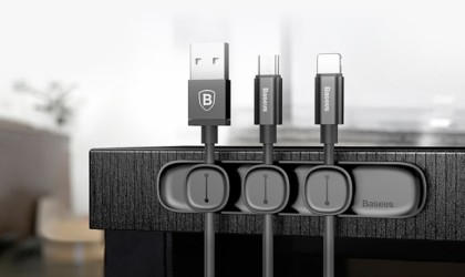 Three black charging cords with black useful office gadgets magnet clips holding them to a black base.